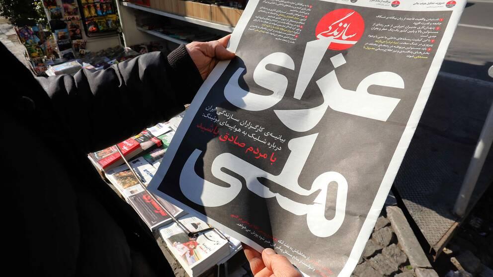 """En iransk man läser en lokaltidning med rubriken """"Nationell sorg"""". Artikeln uppges handla om nedskjutningen av det ukrainska passagerarflygplanet med 176 personer ombord."""