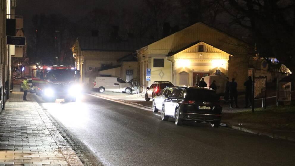 Polisbilar och brandbil vid en byggnad.