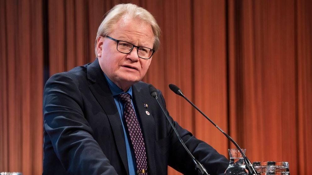 Peter Hultqvist talar från ett podium.