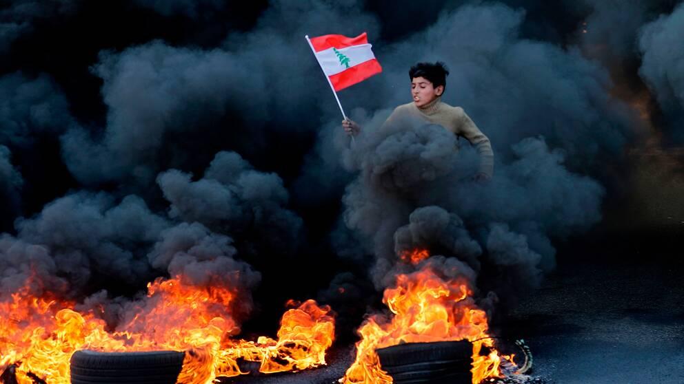 En pojke hoppar över brända bildäck, genom svart rök, med en libanesisk flagga i handen.