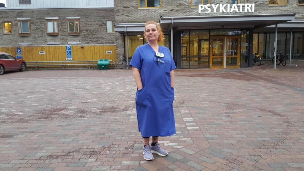 Sjuksköterska står på parkering. Skylt med PSYKIATRI i bakgrunden.