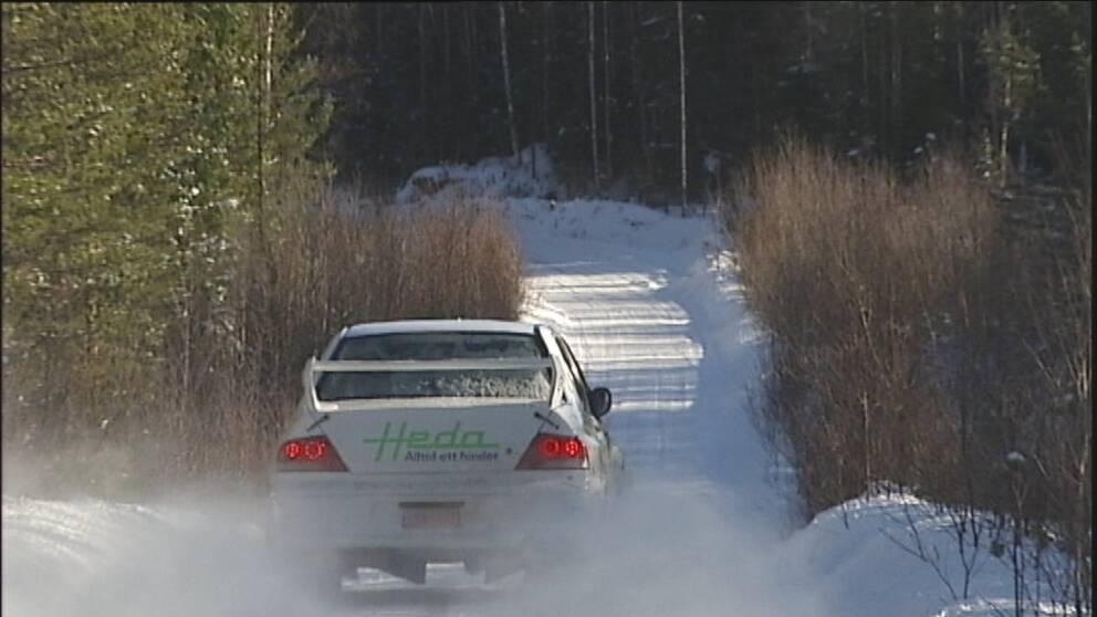 Rallybil på väg på en vintrig skogsväg
