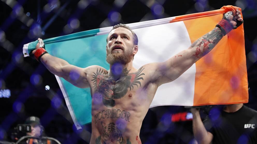 Conor McGregor håller stolt upp den irländska flaggan efter segern.