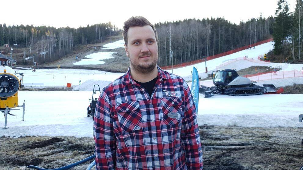 Rickard står vid slalombacken. I bakgrunden ser man en backe som bara har fläckar av snö och en annan backe där man kan åka slalom.