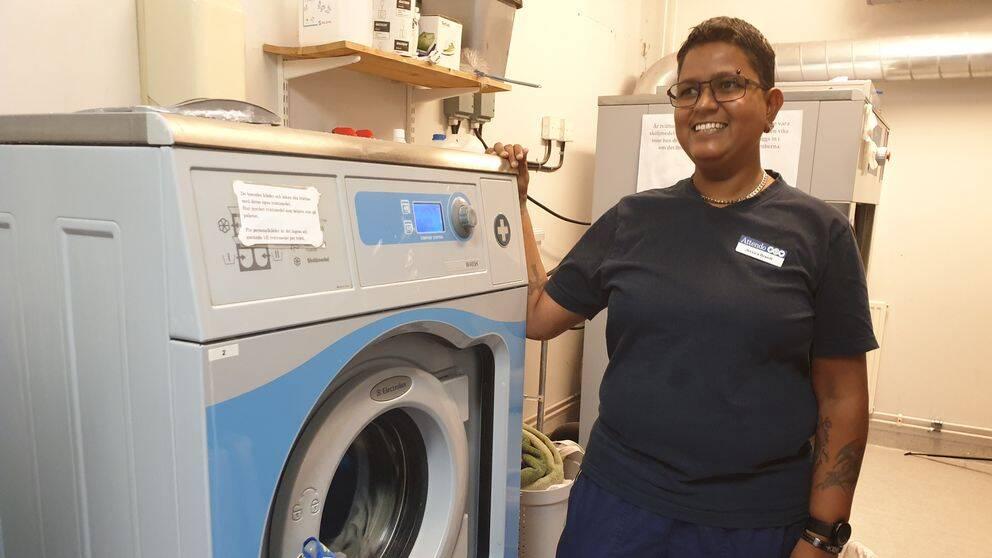 Jessica står i tvättstugan klädd i arbetskläder på ett äldreboende. Hon ler.