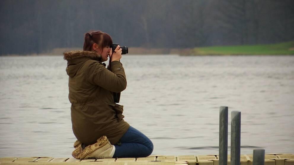 Jennipher sitter på knä på en brygga och fotograferar med en systemkamera.