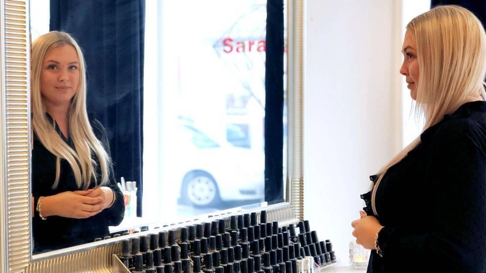 Ung tjej tittar in mot kameran genom en spegel.