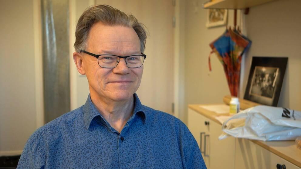 En småleende man med blåspräcklig skjorta, glasögon och bakåtriktat hår sittandes på ett kontor