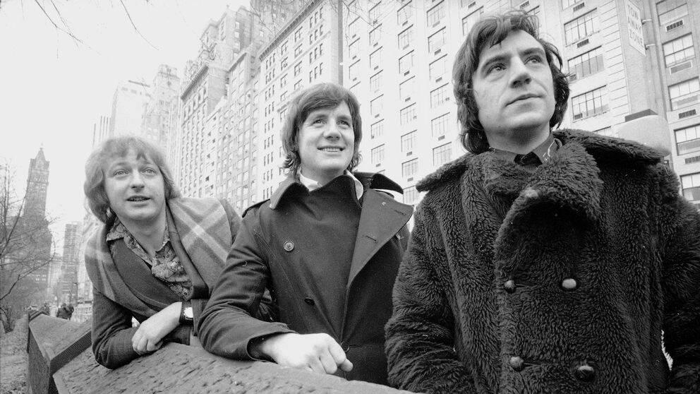 Svartvitt foto på Graham Chapman, Michael Palin och Terry Jones som står i en stadsmiljö.