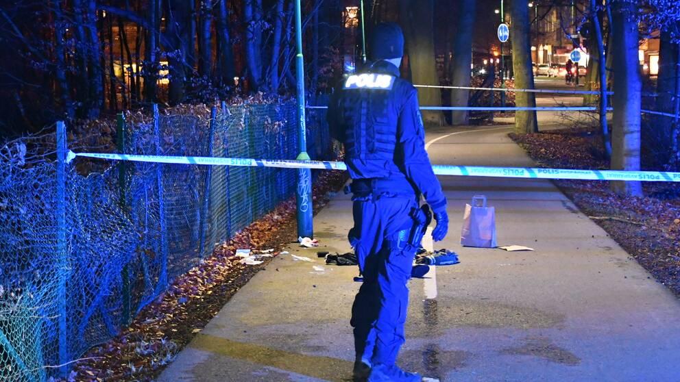 En polis står med ryggen mot kameran framför ett avspärrat området.