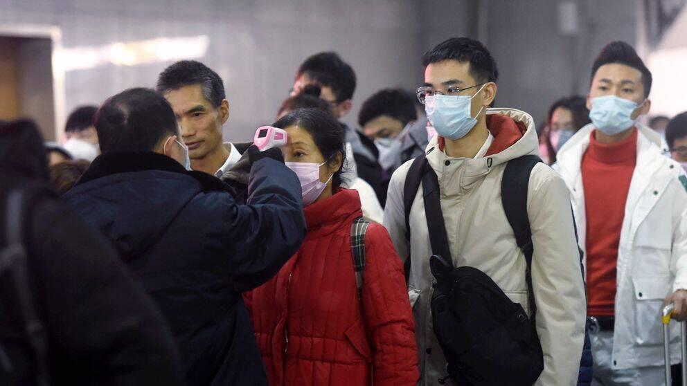 Personal använder termometer för att kontrollera temperaturen på passagerare som anländer från Wuhan på en tågstation i Hangzhou.