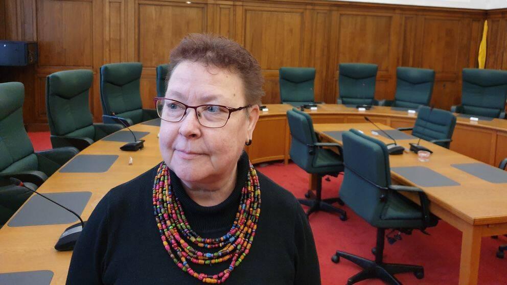 Mia Sköld står i kommunstyrelsens sammanträdesrum med ett runt bord och gröna stolar i bakgrunden.