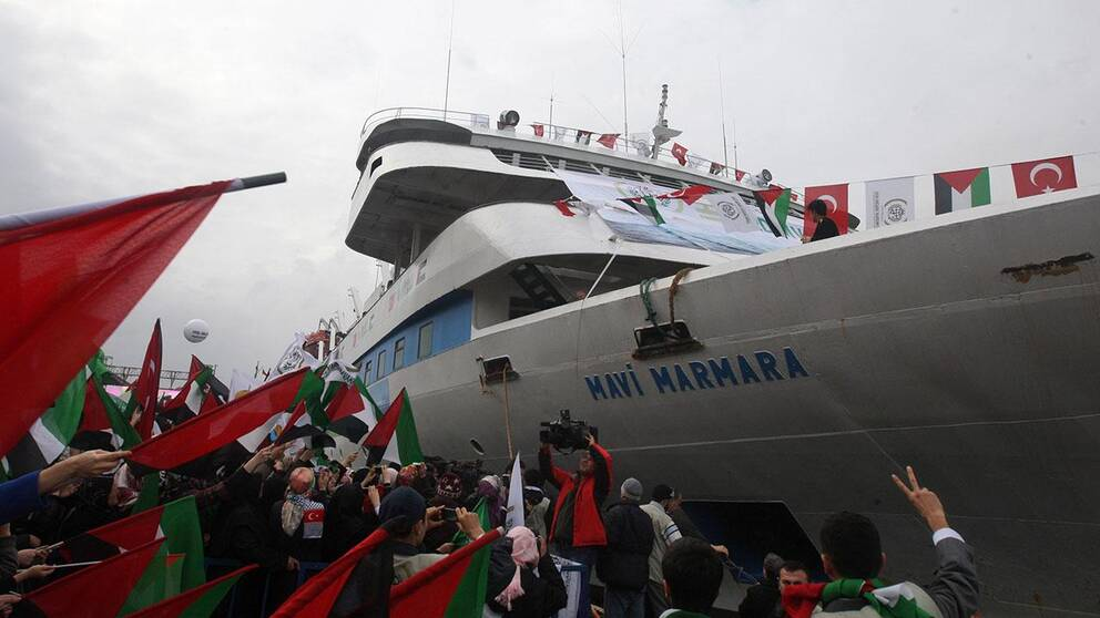 In this Sunday, Dec. 26, 2010 file photo, people holding Turkish and Palestinian flags cheer as the Mavi Marmara ship, the lead boat of a flotilla headed to the Gaza Strip which was stormed by Israeli naval commandos in a predawn confrontation in the Mediterranean on May 31, 2010, arrives back in Istanbul, Turkey. Turkey said Friday Sept. 2, 2011 it was expelling the Israeli ambassador and cutting military ties with Israel over the last year's deadly raid on a Gaza-bound aid flotilla, further souring the key Mideast relationship between Turkey and Israel.(AP Photo/Burhan Ozbilici, File)