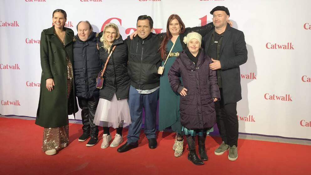 sju personer, inklusive skådespelare från Glada Hudik, på röda mattan