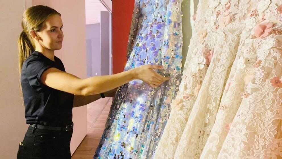Halvbild på Frida Jonsvens som påtar med en klänning.