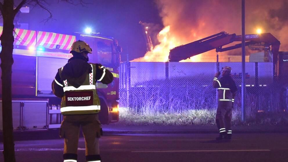 Två personer från Räddningstjänsten framför brinnande lastbilar