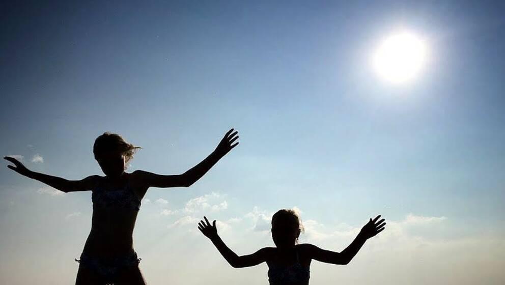 Barn hoppar ur havet.