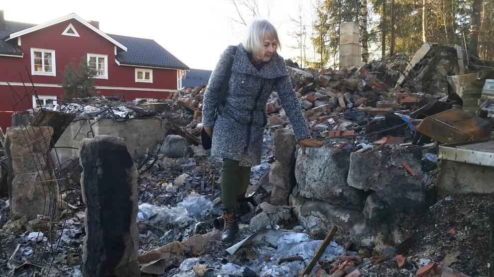 Helbild på Berit Forsberg när hon går omkring bland bråte.