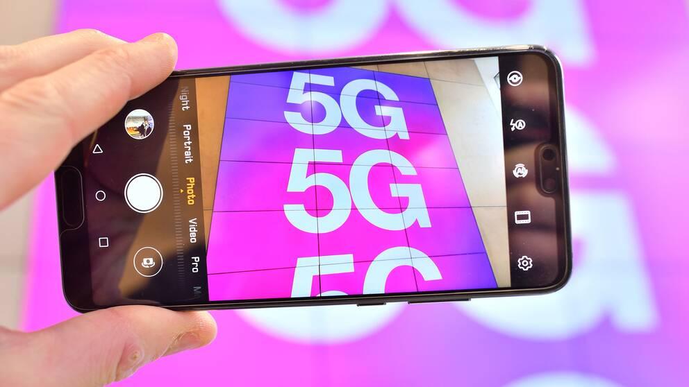 En mobiltelefon riktar kameran mot en skylt som gör reklam för 5G