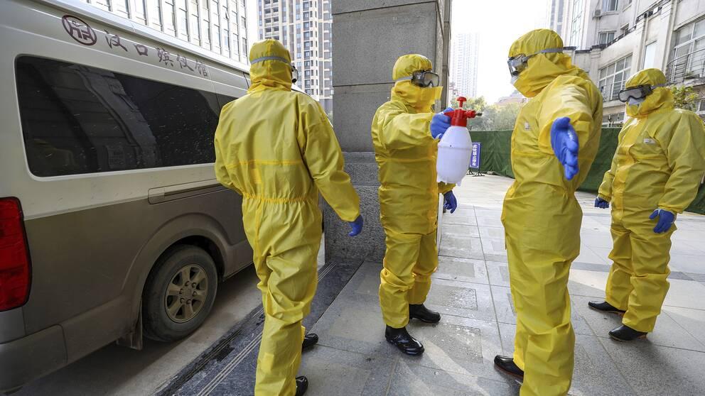 Begravningsarbetare desinficerar sig efter att hanterat en coronasmittad person i Wuhan.
