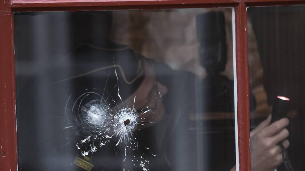 Skotthål i fönster. Polis gör brottsplatsundersköning.