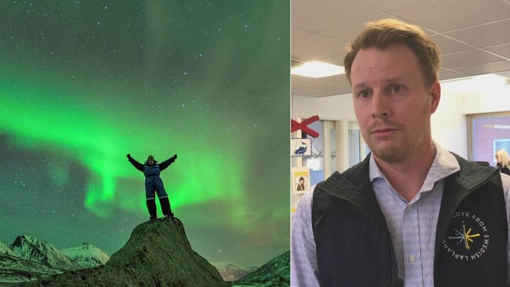 en man i overall står med lyfta armar på en liten bergstopp med halvsnöiga fjäll i bakgrunden och stort norrsken på himlen