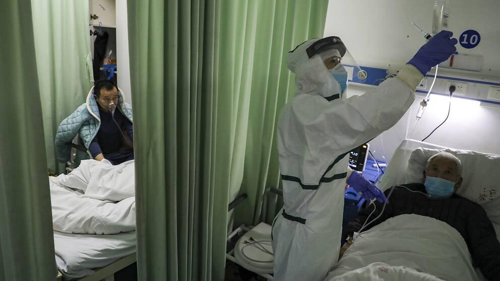 En sjuksköterska administrerar medicin till en patient på ett sjukhus i Wuhan, Kina.