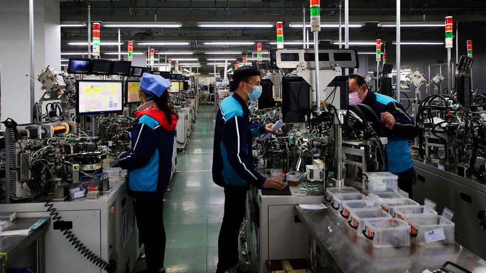 tre fabriksarbetare står framför datorer och jobbar. Alla bär munskydd och marinblåa arbetskläder.