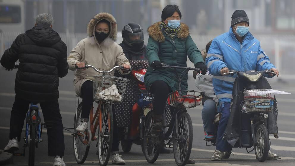 Maskklädda cykeltrafikanter i Kinas huvudstad Peking på torsdagen.