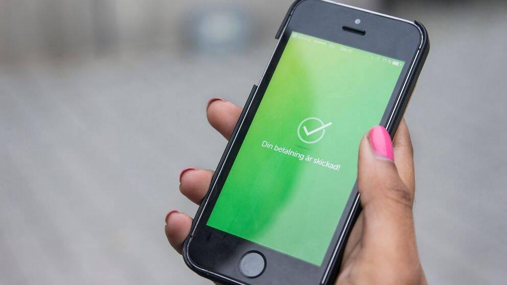 En hand som håller i en mobiltelefon som betalar med swish.