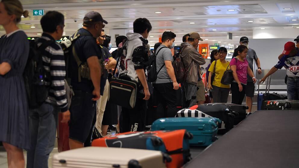 Personer står och väntar på bagage på flygplats.