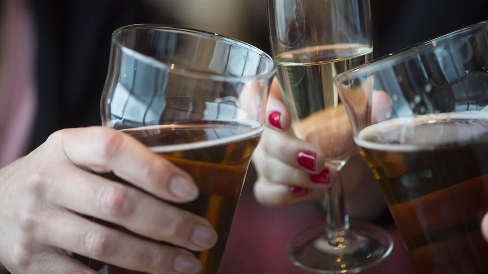 Personer som dricker öl och vin skålar med varandra.