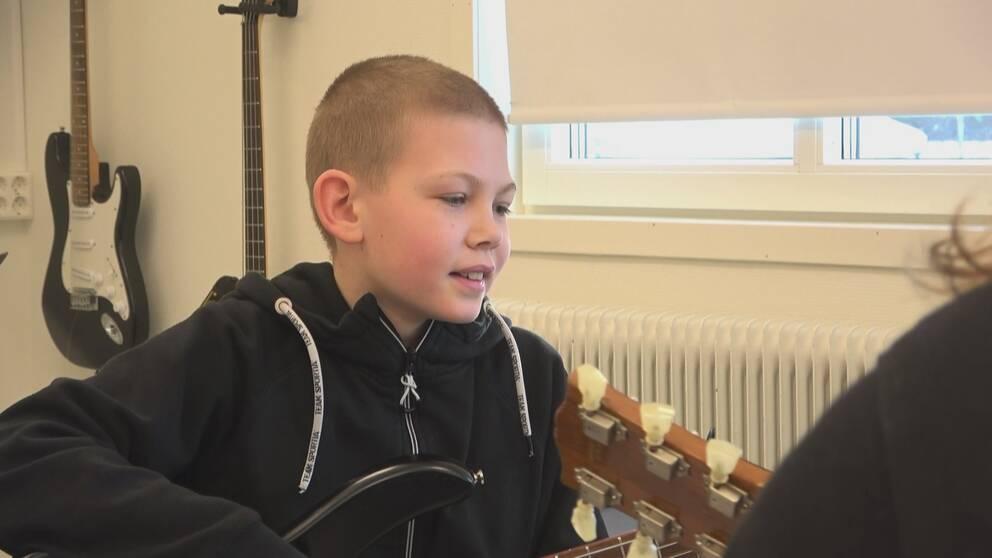 Pojke sitter och spelar elbas