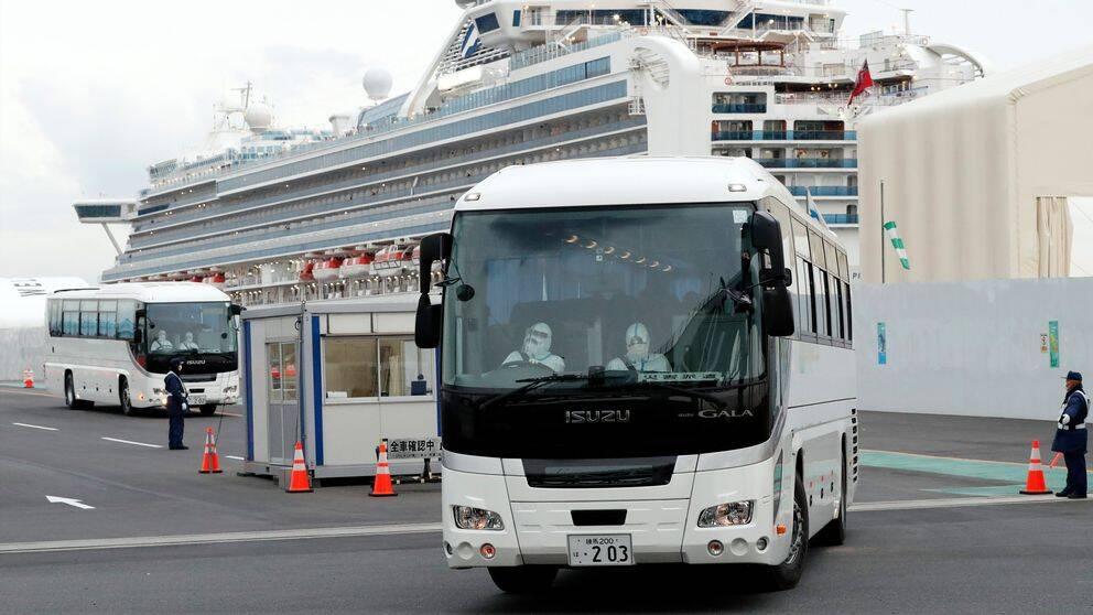 En buss med passagerare som varit ombord på Diamond Princess får lämna hamnen i Yokohama i Japan. I bakgrunden syns fartyget.
