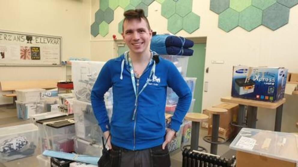 Sam står i blå träningsjacka bland plastlådor med prylar som ska packas upp, med armarna i sidorna.