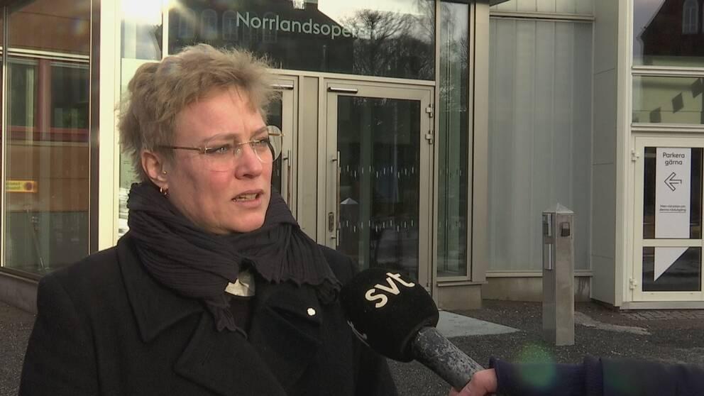 Kvinna med kort ljust hår blir intervjuad utanför Norrlandsoperan