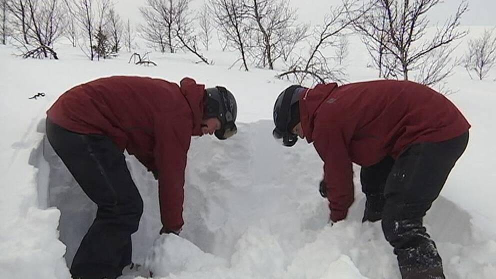 Två personer står och gräver i en snödriva