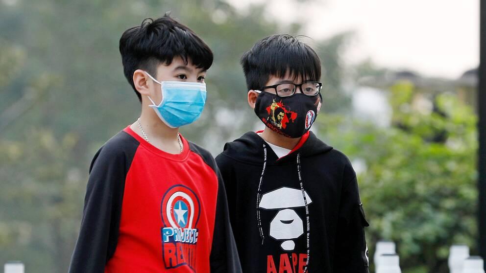 Barn med ansiktsmasker i Hanoi i Vietnam