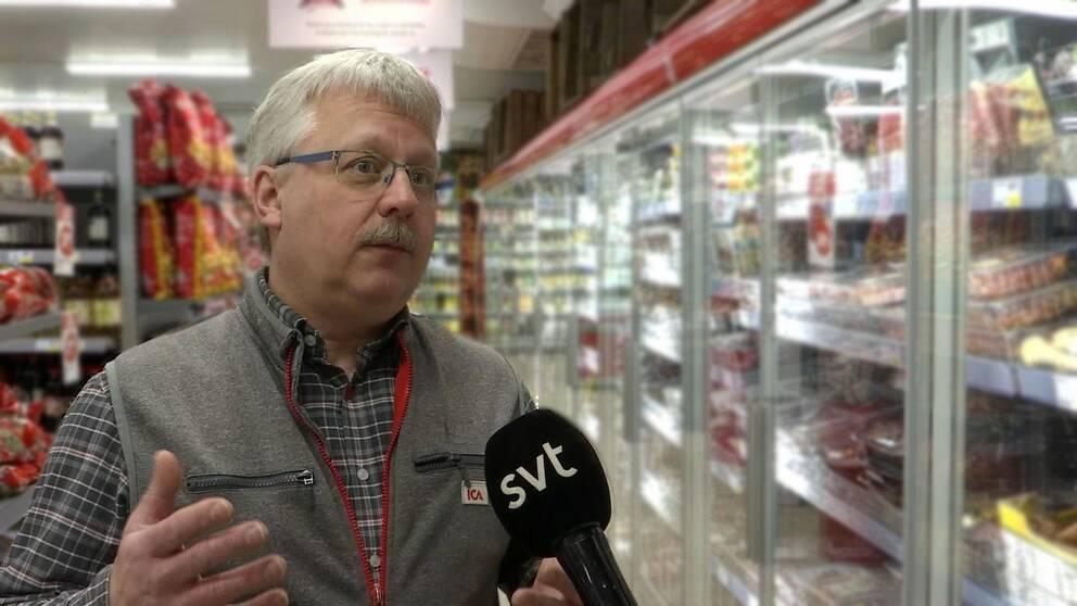 Man med mustasch och glasögon står i en matbutik med en mikrofon framför ansiktet.