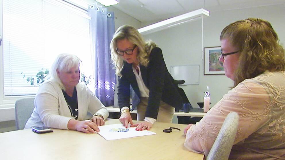 Två kvinnor sitter vid ett bord. En kvinna står mellan dem och pekar på ett papper som ligger på bordet.
