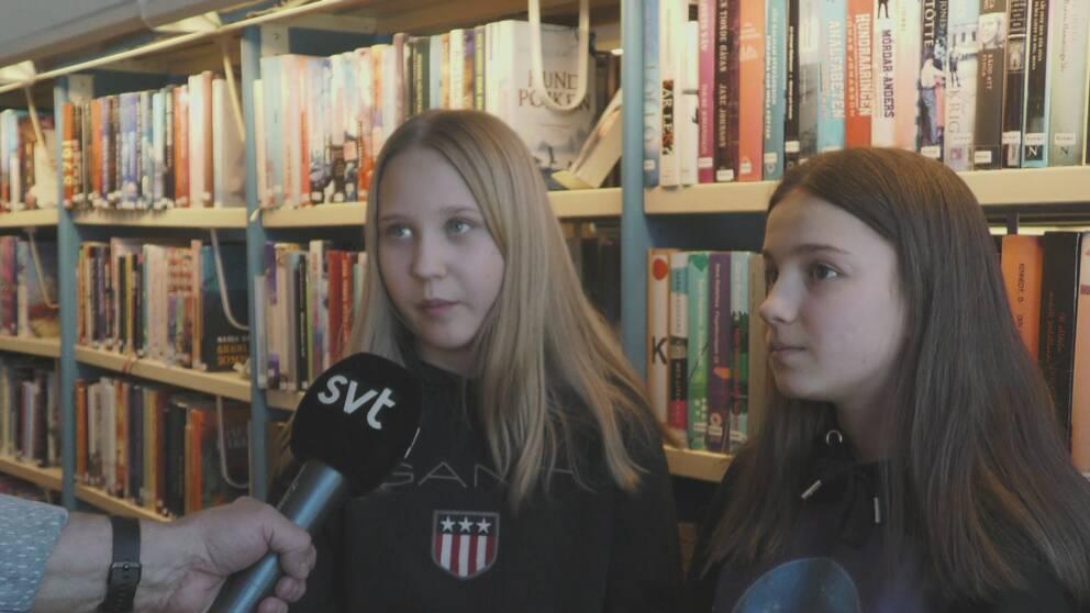 Två ungdomar en tjej med blont långt hår till vänster, en tjej med brunt långt hår till höger