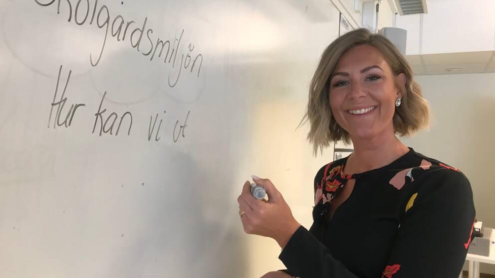 Kvinna skriver på whiteboard-tavla i klassrum.