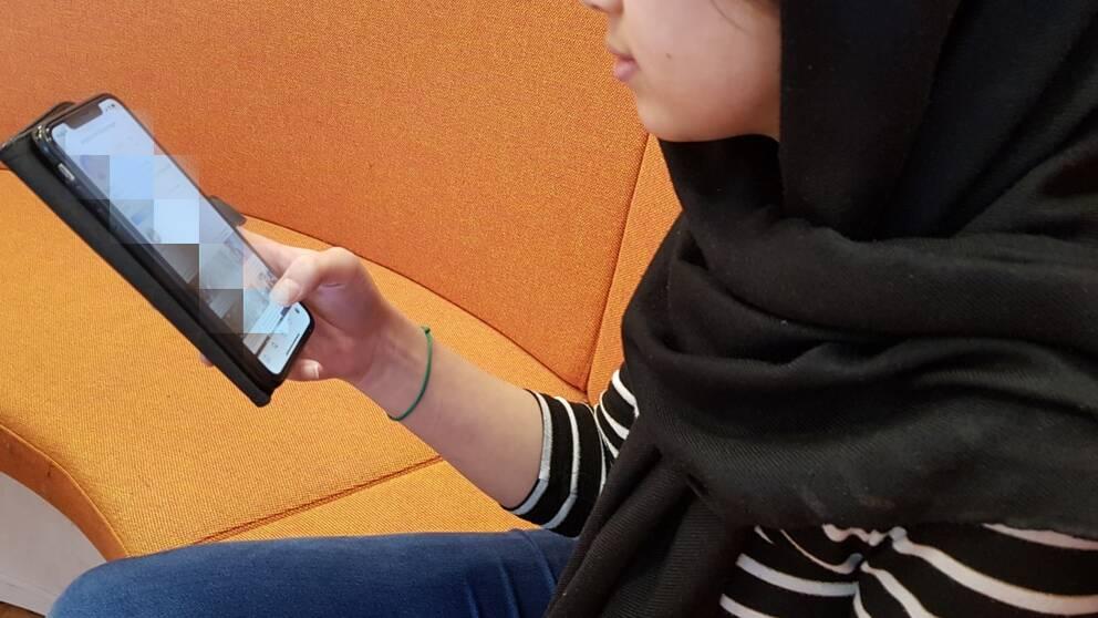 En tjej tittar i sin mobil.