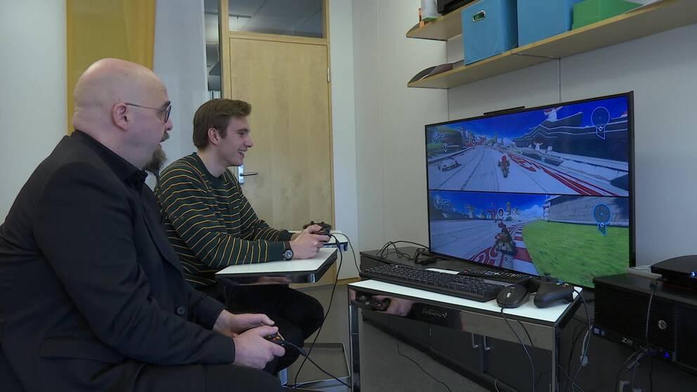 Två män som spelar tv-spel.