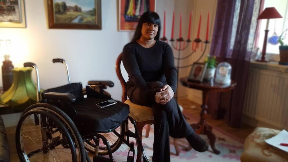 Kvinna sitter på en stol i ett vardagsrum med en rullstol bredvid sig.