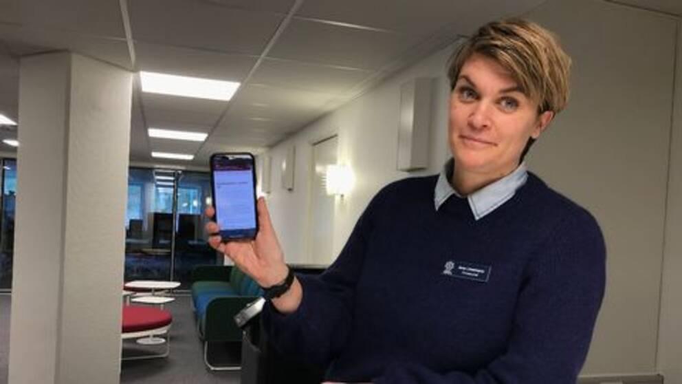 Anna Löwenhamn håller upp en mobiltelefon.