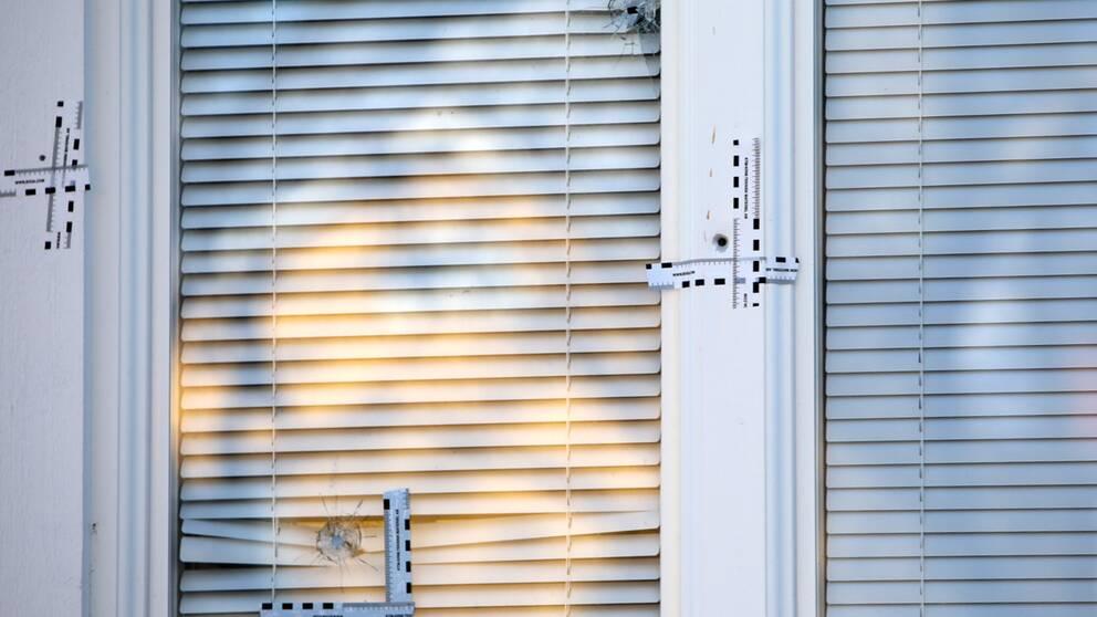 Fönsterruta med hål, persienn som är neddragen.