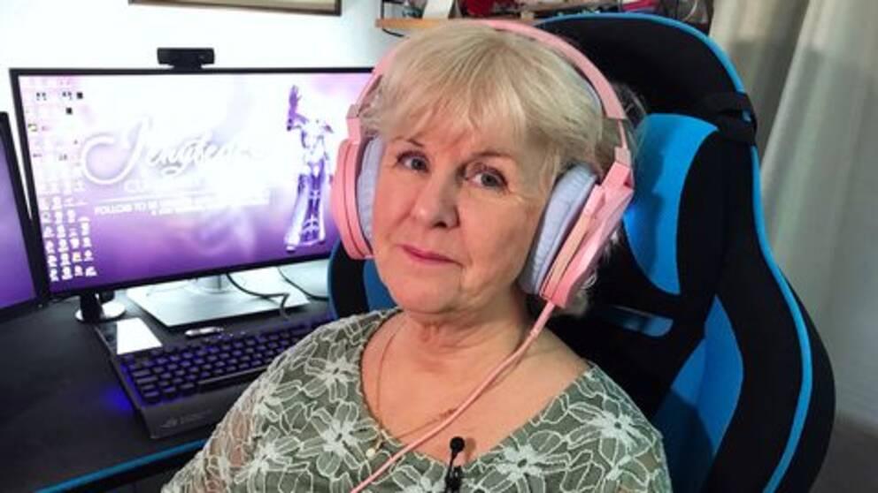 Äldre kvinna med hörlurar framför datorn.