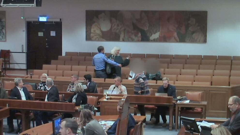 Övervakningsbild från kommunfullmäktige som visar hur en av aktivisterna blir bortförd av ordningsvakt.