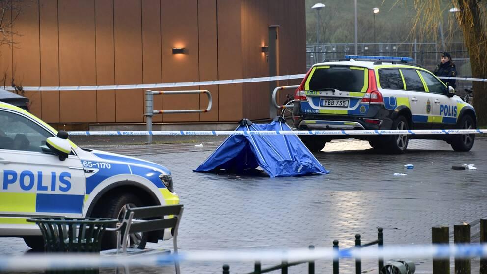 Två polisbilar och ett tält för att skydda bevismaterial.